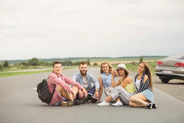 Uśmiechnięci młodzi przyjaciele siedzi na wiejskiej drodze