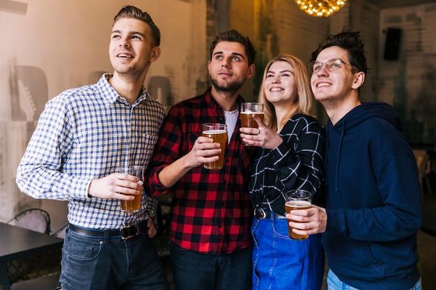 Uśmiechnięci młodzi przyjaciele trzyma szkła piwo ogląda coś