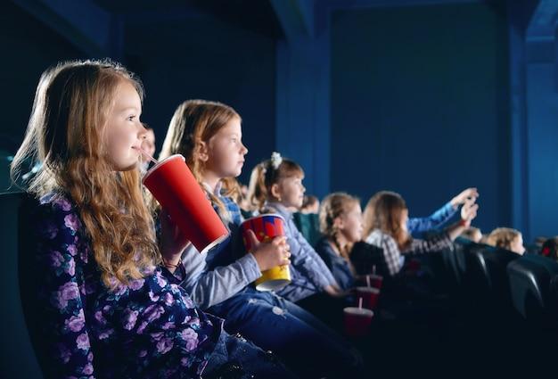 Uśmiechnięci młodzi widzowie je popkorn i ogląda kreskówkę w kinie.