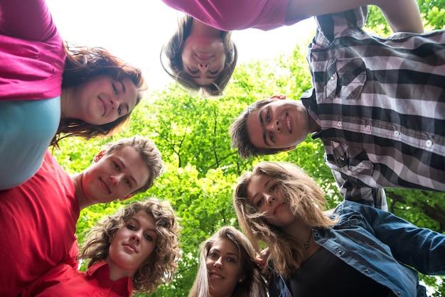 Uśmiechnięci nastolatkowie patrzeje w dół