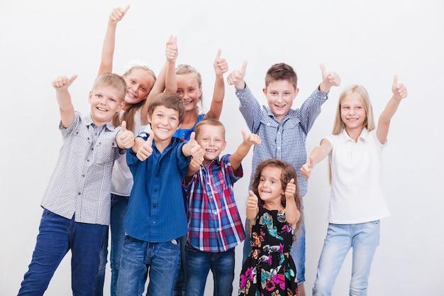 Uśmiechnięci nastolatkowie pokazujący znak porządku na białym?