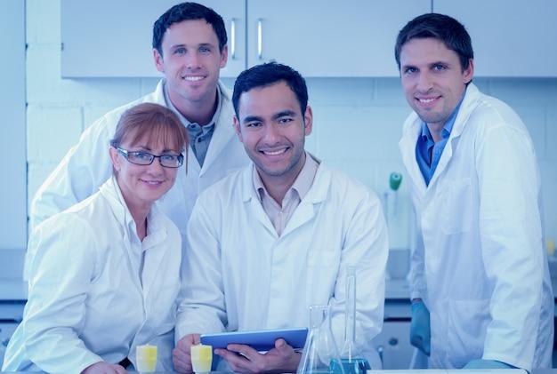 Uśmiechnięci naukowcy z pastylka pecetem w lab