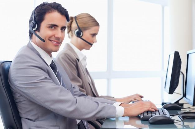 Uśmiechnięci operatorzy korzystający z komputera