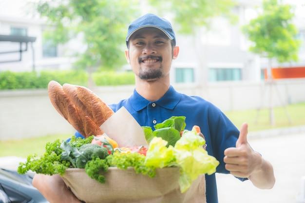 Uśmiechnięci panowie dobrzy i szybko dostarczają produkty spożywcze do domu klienta, zakupy online podczas kwarantanny koronawirusa covid-19, jedzenie w eko papierowej torbie, praca z sercem