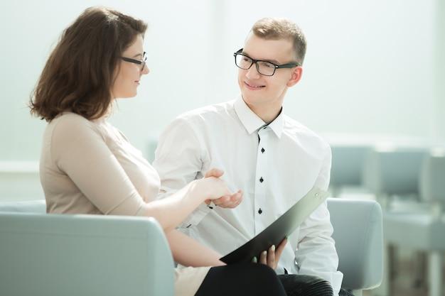 Uśmiechnięci partnerzy biznesowi, ściskając ręce, siedząc w biurze. koncepcja współpracy