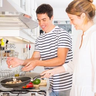 Uśmiechnięci potomstwa dobierają się narządzanie warzywa w smaży niecce