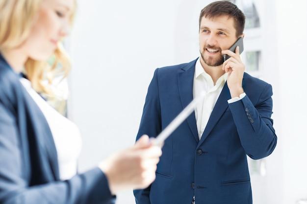Uśmiechnięci pracownicy biurowi płci męskiej i żeńskiej z laptopem i telefonem