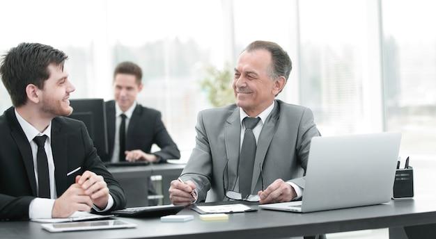 Uśmiechnięci pracownicy pracujący z dokumentami finansowymi w biurze