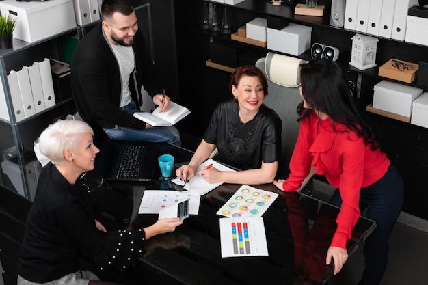 Uśmiechnięci pracownicy rozmawiają w miejscu pracy