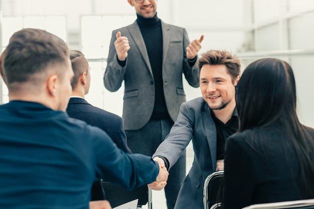 Uśmiechnięci pracownicy ściskają ręce podczas spotkania roboczego. pomysł na biznes
