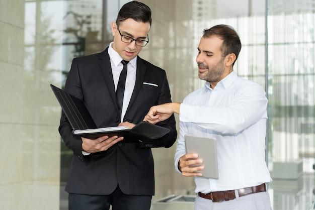 Uśmiechnięci przedsiębiorcy dyskutuje biznesowego dokument w falcówce