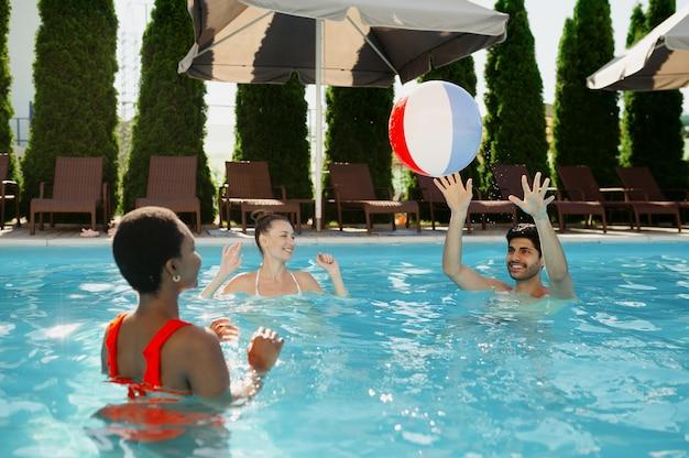 Uśmiechnięci przyjaciele bawią się piłką w basenie