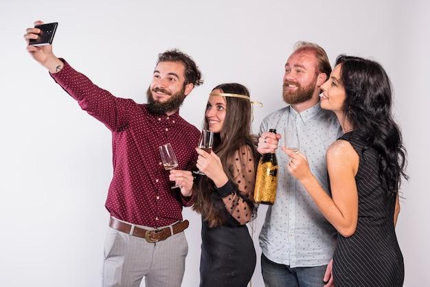 Uśmiechnięci przyjaciele bierze selfie na świętowaniu