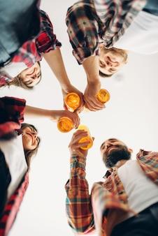 Uśmiechnięci przyjaciele brzęczą butelkami z piwem, widok z dołu, domowe przyjęcie. dobra przyjaźń, grupa ludzi spędza razem wolny czas. wesoła firma celebruje to wydarzenie