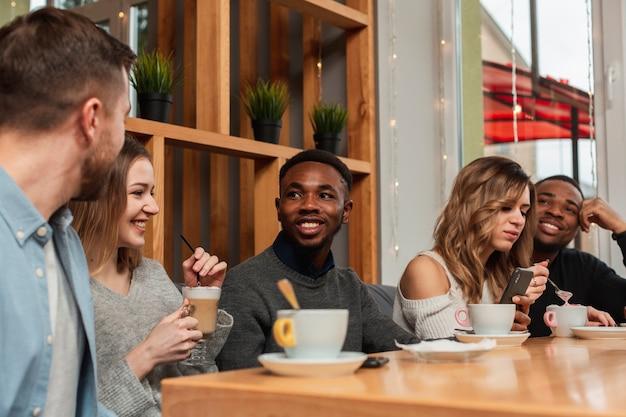 Uśmiechnięci przyjaciele cieszy się filiżankę kawy