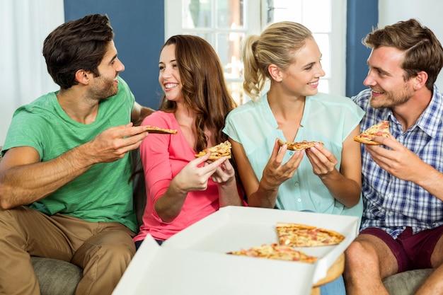Uśmiechnięci przyjaciele cieszy się pizzę
