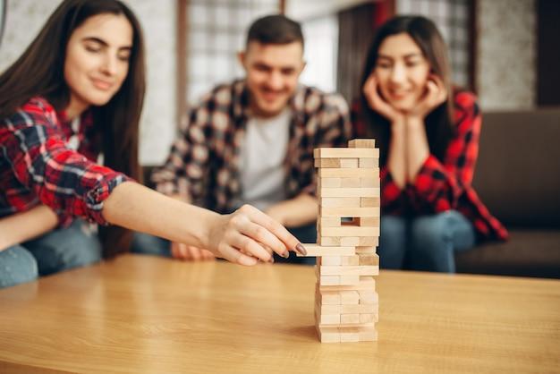 Uśmiechnięci przyjaciele grają jengę w domu, selektywnie skupiają się na wieży.