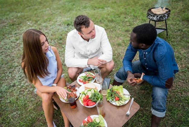 Uśmiechnięci przyjaciele jedzą i bawią się przy grillu