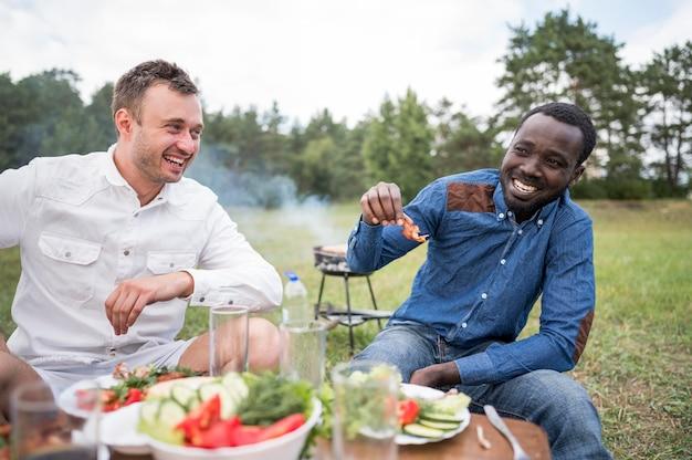 Uśmiechnięci przyjaciele jedzenie grilla na świeżym powietrzu