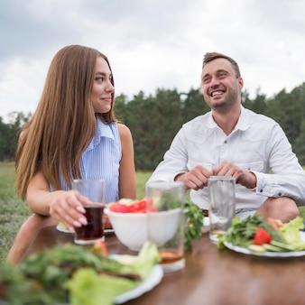 Uśmiechnięci przyjaciele jedzenie na świeżym powietrzu