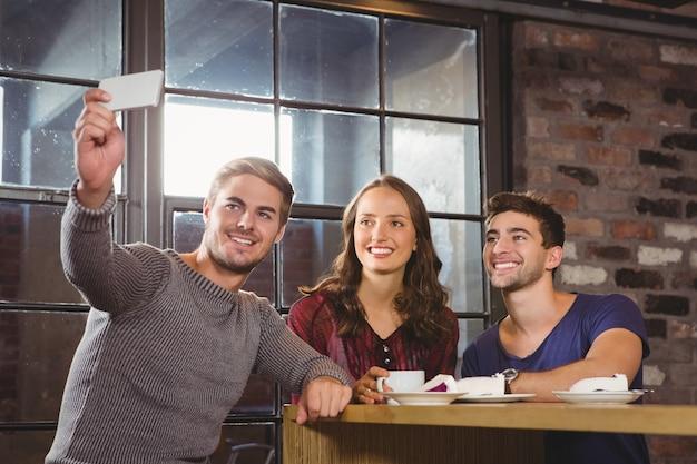 Uśmiechnięci przyjaciele ma kawę i bierze selfies