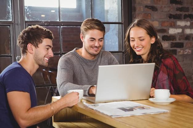Uśmiechnięci przyjaciele ma kawę wpólnie i patrzeje laptop