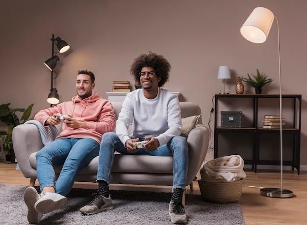 Uśmiechnięci przyjaciele na kanapie grając w gry