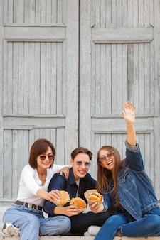Uśmiechnięci przyjaciele na zewnątrz mający hamburgery
