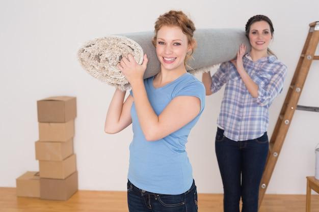 Uśmiechnięci przyjaciele niesie staczającego się dywanik po ruszać się w domu