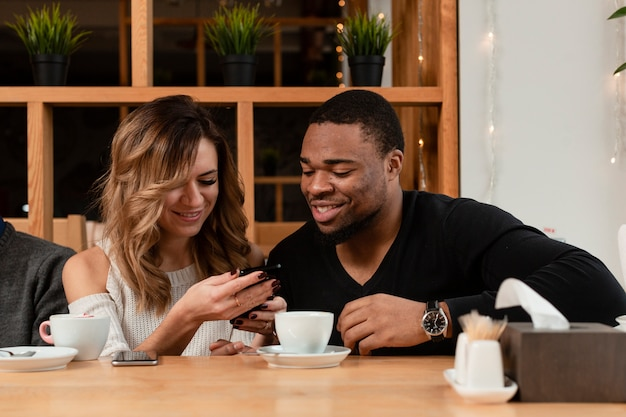 Uśmiechnięci przyjaciele patrząc na telefon
