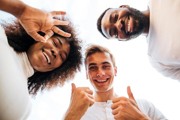 Uśmiechnięci przyjaciele patrząc w dół do aparatu