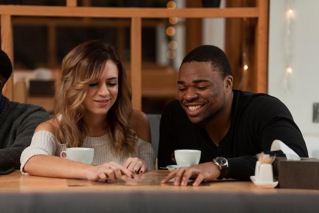Uśmiechnięci przyjaciele pije kawę