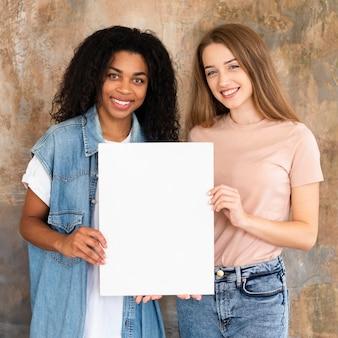 Uśmiechnięci przyjaciele pozowanie razem i trzymając pusty plakat