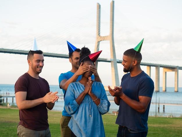 Uśmiechnięci przyjaciele robi niespodziance dla skupionej kobiety