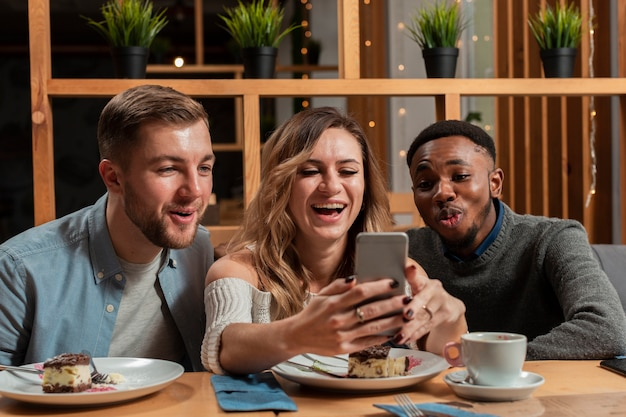 Uśmiechnięci przyjaciele robią selfie
