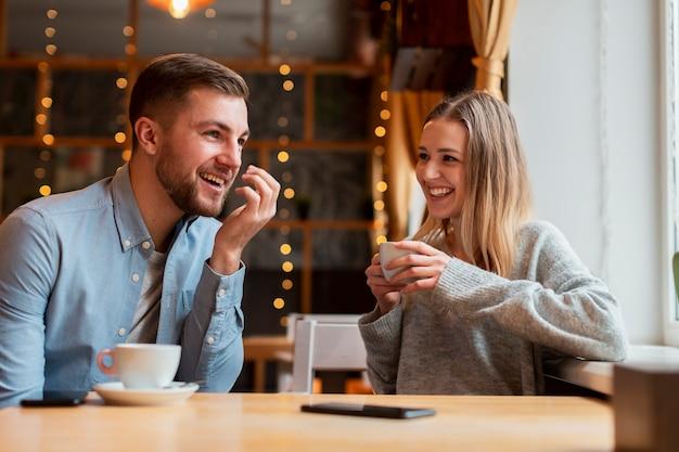 Uśmiechnięci przyjaciele rozmawiają i piją kawę
