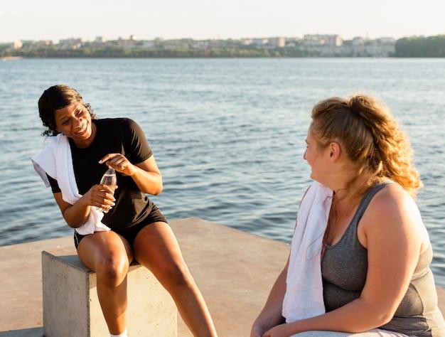 Uśmiechnięci przyjaciele rozmawiający nad jeziorem po treningu
