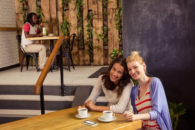 Uśmiechnięci przyjaciele siedzi przy stołem