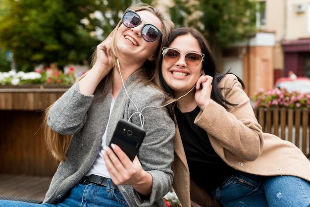 Uśmiechnięci przyjaciele słuchający muzyki