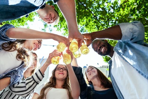 Uśmiechnięci przyjaciele świętują urodziny na świeżym powietrzu w gorący słoneczny letni dzień