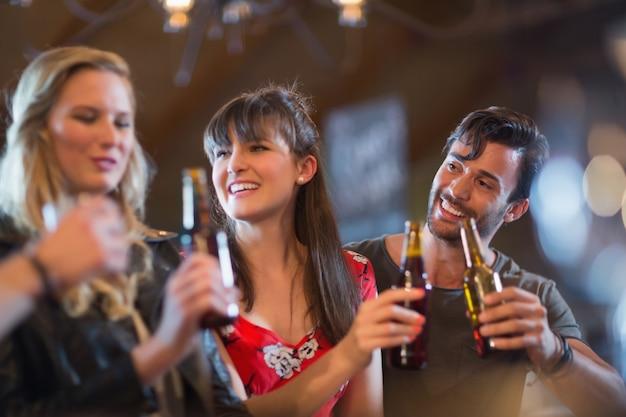 Uśmiechnięci przyjaciele trzymając butelki piwa