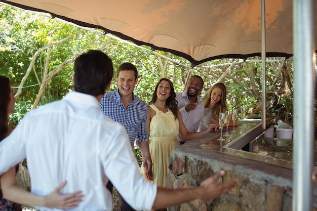 Uśmiechnięci przyjaciele wchodzący w interakcje mając szampana przy ladzie