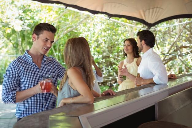 Uśmiechnięci przyjaciele wchodzący w interakcje przy koktajlu przy ladzie