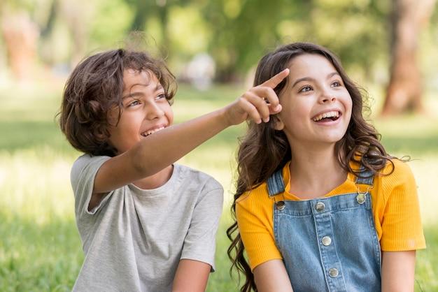 Uśmiechnięci przyjaciele wskazujący na zewnątrz