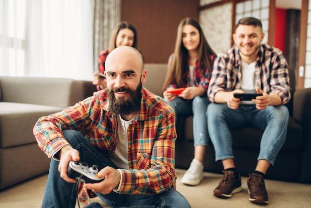 Uśmiechnięci przyjaciele z joystickami grają na konsoli telewizyjnej w domu.