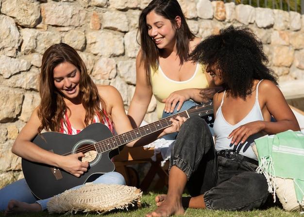 Uśmiechnięci przyjaciele ze średnim strzałem gitary