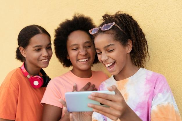 Uśmiechnięci przyjaciele ze średnim strzałem z telefonem