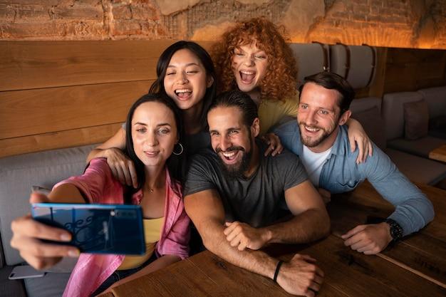 Uśmiechnięci przyjaciele ze średnim ujęciem robiący selfie