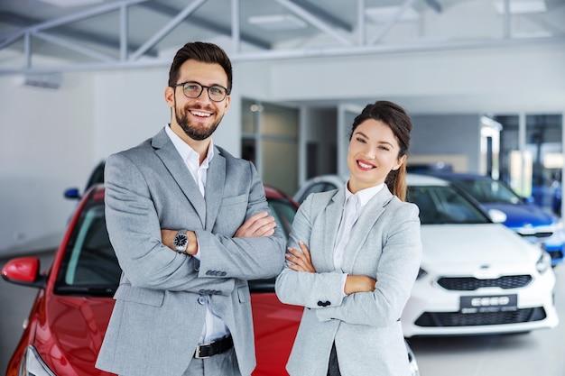 Uśmiechnięci, przyjaźni sprzedawcy samochodów stojący w salonie samochodowym z założonymi rękami i ogłaszający sprzedaż detaliczną.