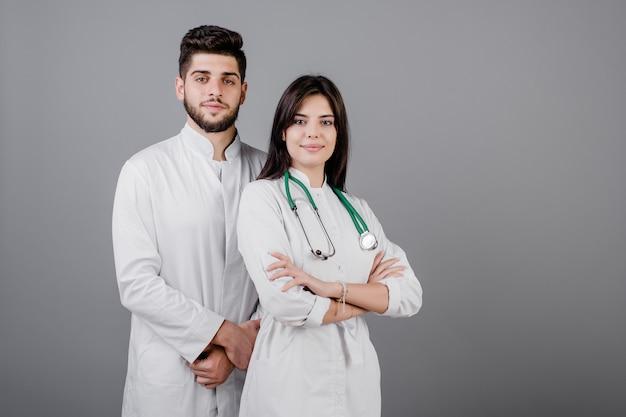 Uśmiechnięci przystojni lekarze medycyny w kontuszy ono uśmiecha się odizolowywam nad popielatym